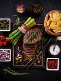 Beef steak on wooden table. Delicious beef steak on wooden table, close-up Stock Photos