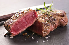 Beef Steaks on black Slate. Beef steaks as closeup on a black slate Royalty Free Stock Photo