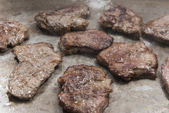 Beef steaks cooking on graill at at restaurant buffet Royalty Free Stock Photo