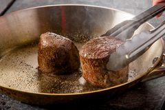 Beef steaks are fried in a frying pan in a restaurant stock images