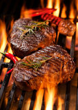 Beef steaks on the grill. With flames royalty free stock photo