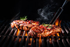 Beef steaks on the grill. With flames Stock Image