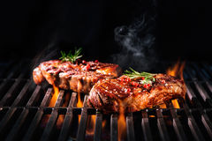 Beef steaks on the grill. With flames Royalty Free Stock Photography