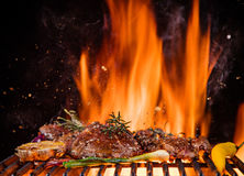 Beef steaks on the grill with flames Royalty Free Stock Images