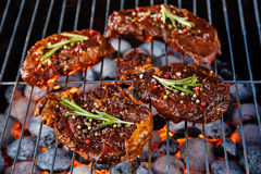 Beef steaks on the grill grate with fiery coals. Barbecue, grill and food concept Stock Images
