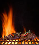 Beef steaks on the grill grate, flames on background. Barbecue and grill, delicious food Stock Photos