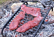 Beef steaks on the grill. Raw beef steaks on the grill for barbecue Stock Images