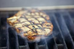 Beef steaks on the grill with smoke. Beef steaks on the grill with smoke Royalty Free Stock Photography