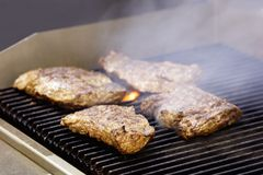 Beef steaks on the grill with smoke Stock Images