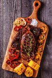 Beef steaks with grilled tomatoes, mushrooms and corn. royalty free stock photo