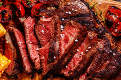 Beef steaks with grilled tomatoes, mushrooms and corn. royalty free stock images