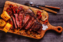Beef steaks with grilled tomatoes, mushrooms and corn. Stock Photo
