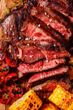 Beef steaks with grilled tomatoes, mushrooms and corn. royalty free stock photos