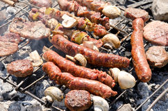 Beef steaks and sausages cooking in open flame. On barbecue grill Stock Photography