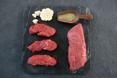 Beef steaks, spices and garlic on slate plate Stock Images