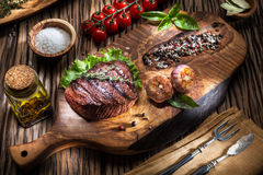 Beef steaks with spices on a wooden tray. Stock Image