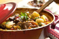Beef Stew. Traditional goulash or beef stew, in red crock pot, ready to serve.  Shallow DOF Stock Photo