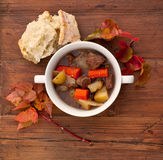 Beef Stew. With bread and leaves on a weathered wooden table Stock Image
