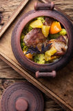 Beef stew in ceramic pot. Baked meat with orange sauce in a rustic ceramic pot Royalty Free Stock Photo