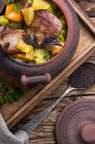 Beef stew in ceramic pot. Baked meat with orange sauce in a rustic ceramic pot Stock Photo