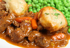 Beef Stew with Dumplings. Casseroled beef stew with suet dumplings and garden peas Stock Photography
