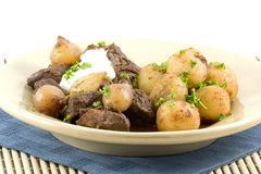 Beef stew, onions, potatoes. Beef stew slow cooked in the oven with pearl onions and wine, served with potatoes royalty free stock images