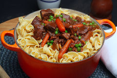Beef Stew Over Egg Noodles. Beef stew with carrots & green peas over egg noodles in dutch oven royalty free stock image