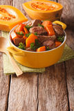 Beef stew with pumpkin, onion and spices close up in a yellow pa Royalty Free Stock Photo
