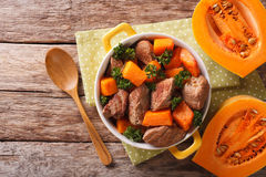 Beef stew with pumpkin, onion and spices closeup in a yellow pan Stock Photo