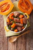 Beef stew with pumpkin, onion and spices closeup in a yellow pan Stock Images