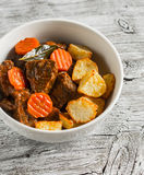 Beef stew with roasted potatoes in a white bowl Stock Photography
