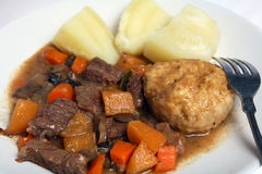Beef stew suet dumpling and potatoes. A typical English-style beef stew, containing carrots, swede (rutabega) and mushrooms, served with suet dumpling and boiled Stock Photos
