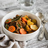 Beef stew in tomato sauce and roasted potatoes in a white bowl Stock Image