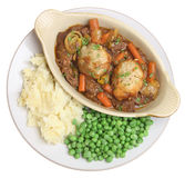 Beef Stew with Vegetables Meal. Beef stew with suet dumplings in an individual casserole dish with mashed potato and peas Stock Photography