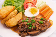 Beef stew with wedges potato, boiled eggs, cucumber, carrot, lettuce, and tomato. In white background Stock Photos