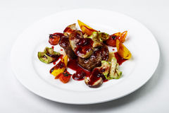 Beef stewed with vegetables and sauce on round plate on white ba Royalty Free Stock Images