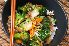 Beef Stir-Fry. With broccoli, carrots, onions, peppers, sesame seeds, and ginger on rice Stock Images