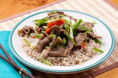 Beef stir fry. Orange and ginger beef stir fry over brown rice Royalty Free Stock Photos