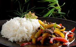 Beef stir-fry with vegetable and rice. On the black plate Royalty Free Stock Photo