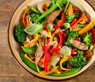 Beef stir fry with vegetables on  wooden table. Royalty Free Stock Image