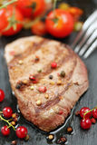 Beef on a stone with berries and tomatoes Stock Photo