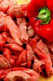 BEEF STRIPS. And red pepper on cutting board Royalty Free Stock Image