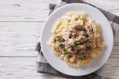 Beef stroganoff with pasta fusilli . Horizontal top view Royalty Free Stock Photo