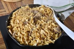 Beef Stroganoff in a Skillet. Beef Stroganoff in a cast iron skillet with a serving spoon Stock Photography