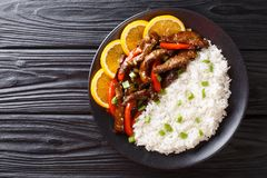 Beef with sweet peppers in orange glaze served with rice close-up. Horizontal top view. Beef with sweet peppers in orange glaze served with rice close-up on a royalty free stock photos