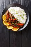 Beef with sweet peppers in orange glaze served with rice close-up. Vertical top view. Beef with sweet peppers in orange glaze served with rice close-up on a stock images