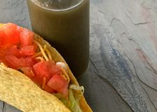 Hard corn shell taco next to green pepper hot sauce royalty free stock photo