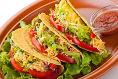 Beef tacos with salad and tomatoes salsa. Closeup of beef tacos served with salad and fresh tomatoes salsa on white background royalty free stock images