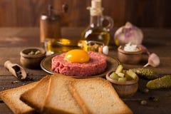Beef tartar on dark wooden table Stock Photo