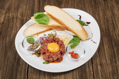 Beef tartar with parmesan cheese. Beef tartare with parmesan cheese, raw egg and a small toast served on a plate on old wooden table Stock Photography